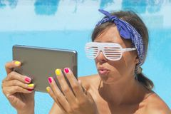 Young girl making selfie by the pool with a tablet Stock Photo