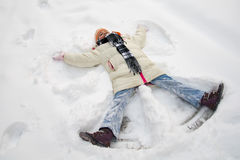 Young girl making a snow angel Stock Photos