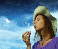 Young girl making soap bubbles. A young girl blowing soap bubbles Stock Photography
