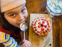 Young girl making strawberry cake Stock Images