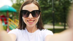 Young girl making video selfie and having fun in the park. stock footage