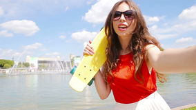Young girl making video selfie and having fun in the park. Lifestyle selfie portrait of young positive woman having fun stock video footage