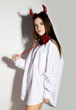 Young girl in a man`s white shirt with red horns holding trident and looks like pretty Devil Royalty Free Stock Image