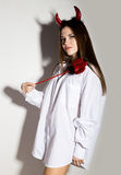 Young girl in a man`s white shirt with red horns holding trident and looks like pretty Devil Stock Photo