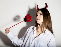 Young girl in a man`s white shirt with red horns looks like pretty Devil Stock Images