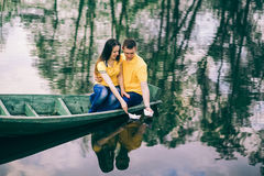 Young girl and man sitting together in old wooden boat on river. Royalty Free Stock Photo