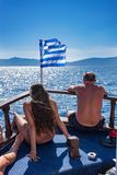 Young girl and man sun bathing in front of Greek flag on boat de. Ck RHODES, GREECE Royalty Free Stock Photography