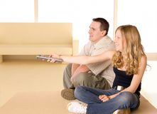 Young Girl And Man Watching TV. Together. Girl is holding a remote controller Stock Images