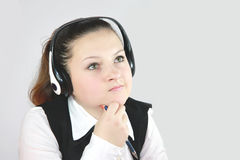 Young girl manager on the headphones. A young office worker girl in headphones operator Royalty Free Stock Photos