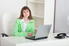 Young girl - manager sits at a table in office Stock Image
