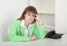 Young girl - manager sits at a table in office Royalty Free Stock Images