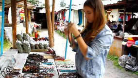 Young girl on the market chooses and tries beads stock video footage