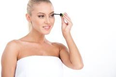 Young girl mascaras her eyelashes in bathroom. Stock Photography