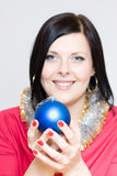 Young girl in x-mass mood. Young brunette girl keep blue Christmass tree bauble Royalty Free Stock Photos