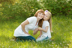 A young girl with mather on a green grass Royalty Free Stock Image