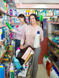 Young girl and mature woman choosing washing detergent Royalty Free Stock Image