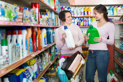 Young girl and mature woman choosing washing detergent Stock Photos