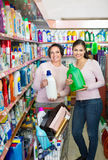 Young girl and mature woman choosing washing detergent stock photo