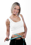 Young girl measuring her belly. Young happy girl measuring her belly Royalty Free Stock Photography