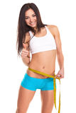 Young girl measuring her waist and being happy Royalty Free Stock Photography