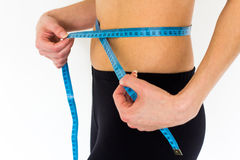 Young girl measuring her waist. Young fit girl measuring her waist Stock Image