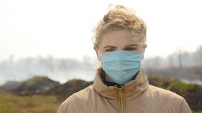 Young girl in a medical mask. Burnt field on the background. Thick smoke. Slow motion. Close-up