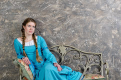 Young girl in medieval dress sits on a banquette Stock Photos