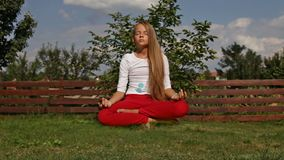 Young girl meditate in lotus position - hovering above the grass, camera slide. Young girl meditate in lotus position - hovering above the grass in the garden stock video