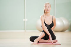 The young girl meditates in sports to a gym Royalty Free Stock Photos
