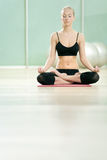 The young girl meditates in sports to a gym Stock Photos