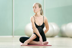 The young girl meditates in sports to a gym Stock Images