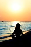 Young girl meditating on beach. Silhouette of young girl meditating on beach Royalty Free Stock Photography