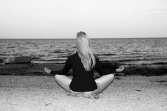 A young girl is meditating on the beach sitting on the shore Stock Image