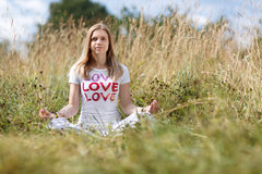 Young girl meditating in the field Stock Image