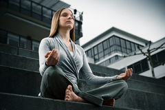 Young girl meditating. In a modern environment stock images