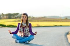 Young girl meditating outdoors. Stock Image