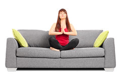 Young girl meditating seated on a couch Royalty Free Stock Photo