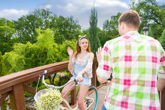 Young girl meeta boy while riding on bikes on footbridge in park Royalty Free Stock Photo