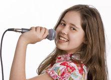 Young girl with microphone singing. Pretty young girl smiling whilst holding a microphone and singing royalty free stock images