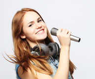 Young girl with microphone sings Royalty Free Stock Images
