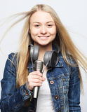 Young girl with microphone sings Royalty Free Stock Image