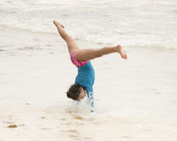 Young girl in middle of a cartwheel on the beach stock photography