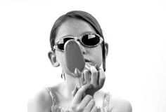 Young girl and mirror. Young girl putting on lipstick looking in handheld mirror Stock Image