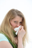 Young girl with a miserable head cold. Blowing her nose in a tissue royalty free stock images