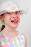 Young Girl Missing Front Teeth. Cute young girl in dressy outfit using tongue to accentuate missing front teeth Stock Image
