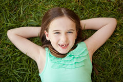 A young girl with a missing tooth is lying on her back on the grass Royalty Free Stock Photos
