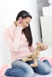 Young girl on mobile holding toy bunny Royalty Free Stock Photo
