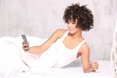 Young girl with mobile phone in bed. Royalty Free Stock Photography