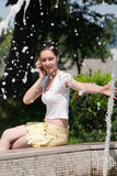 Young girl with a mobile phone at a fountain Stock Photos