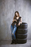 Young girl with a mobile phone, is leaning against the tires on Stock Photos